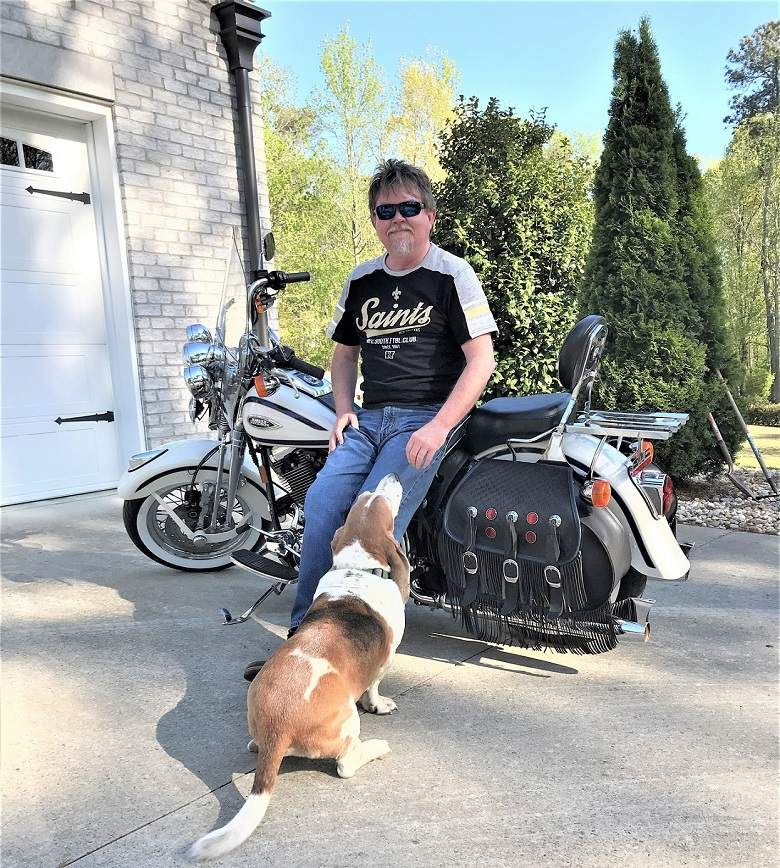 Greg at home with his Bassett Hound, Roscoe and his 97 Harley Spinger he calls Rusty