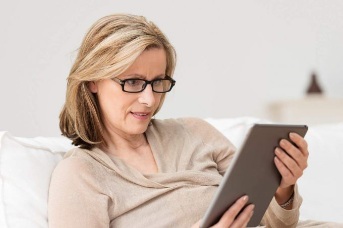 Retirement age woman sitting on couch, reading ipad